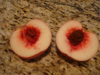 Organic white peach sliced in half on countertop