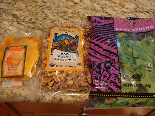 Packages of mango slices, raw walnuts and spring greens on countertop