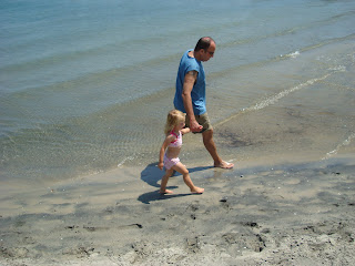 Man and child walking along beach wading in water