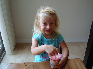 Young girl smiling holding sippy cup full of smoothie mixture