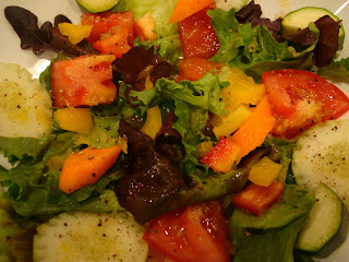Mixed green salad topped with diced vegetables in dressing