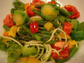 Spiralized zucchini noodles topped with mixed vegetables and dressing