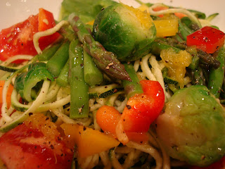 Close up of Spiralized zucchini noodles topped with mixed vegetables and dressing
