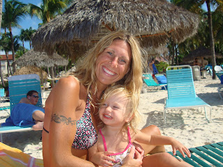 Woman and young girl on beach chair in swimsuits smiling
