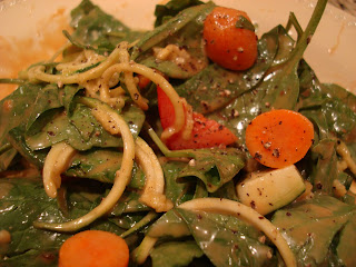Spinach, zucchini noodles, mixed vegetables toped with peanut sauce in bowl