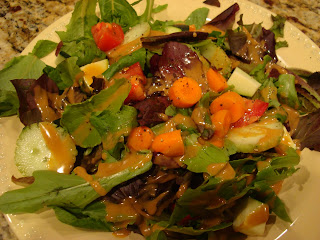 Mixed green salad with vegetables on white plate