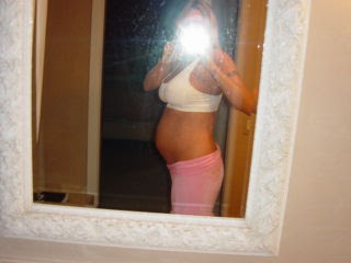 Woman taking pregnancy belly. photo in white mirror