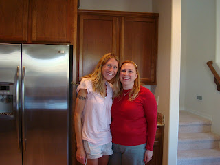 Two women standing in kitchen smiling
