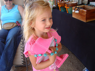 Young girl wearing pink holding a turquoise necklace