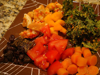 Dinner plate filled with chipped cheese pizza, kale chips and vegetables