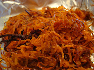 Spiralized sweet potato on foil lined pan out of oven