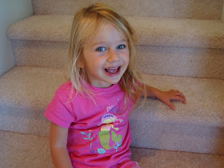 Smiling young girl sitting on steps in pink shirt