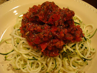 Zucchini Noodles topped with Raw Marinara Sauce on white plate