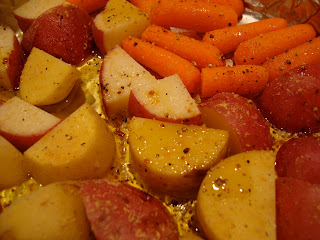 Close up of red and yukon gold potatoes, baby carrots with oil, salt, pepper and ginger in foil lined pan
