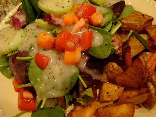Mixed salad with dressing served with roasted potatoes and carrots on plate