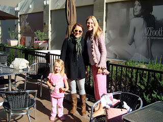 Two women and young girl standing in front of coffee shop