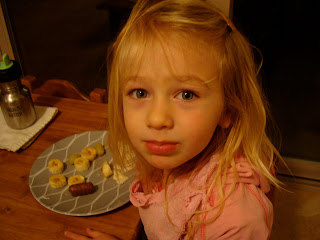 Young girl sitting at table sick eating snacks off of plate