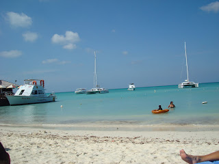 Aruban beach with simmers and boats in water
