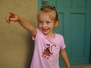 Young girl standing in front of blue door smiling