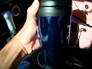 Hand holding coffee in to-go cup