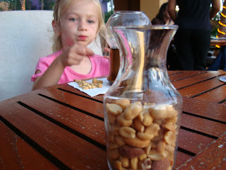 Close up of mixed nuts in jar with young girl in background