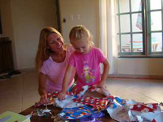 Woman and young girl sitting together unwrapping presents