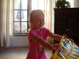Young girl standing in living room opening Christmas Presents