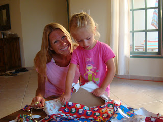 Woman and young girl smiling while girl opens presents