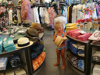 Gift shop with young girl playing with hat
