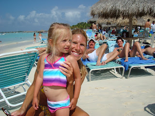 Woman and young girl in swimsuits on beach in Aruba smiling