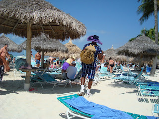 Man walking under palm tree huts on beach