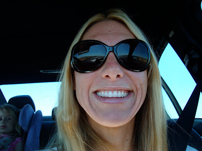 Woman in sunglasses smiling in car