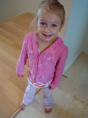 Young girl standing in pink zip up smiling