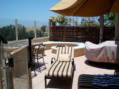 Outside patio with lounge chair and umbrella