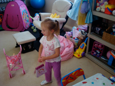 Young girl playing in toy room by dress up clothes