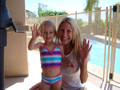 Woman and child in front of pool waving