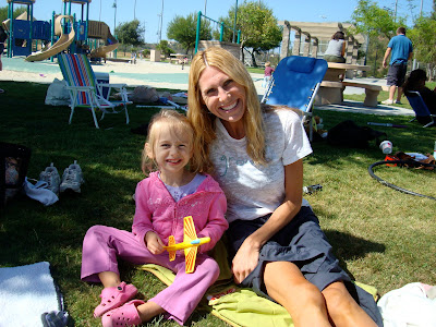 Woman and child sitting on grass outside of pool area
