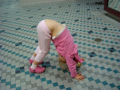 Young girl doing yoga pose on floor