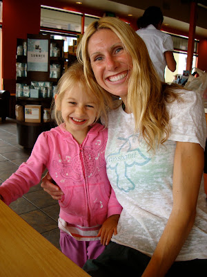 Woman and young girl hugging and smiling at table