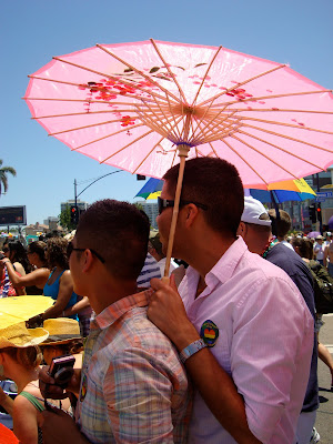 Two men standing under pink parasol