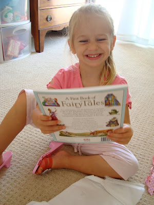 Young girl holding book and smiling