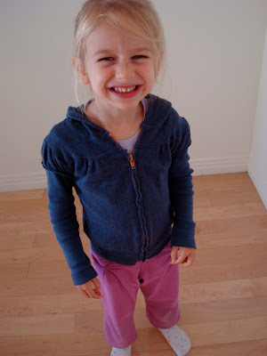 Young girl in blue zip up hoodie smiling