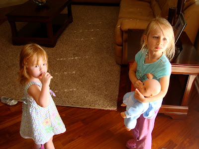Two young girls one holding baby doll