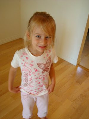Young girl in butterfly t-shirt standing looking at camera
