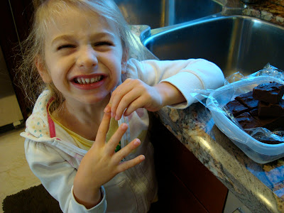 Young girl making silly face with fudge on countertop