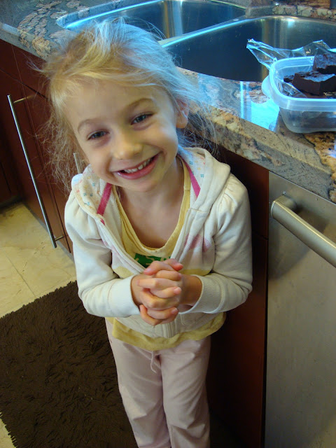 Young girl smiling and clasping hands in kitchen
