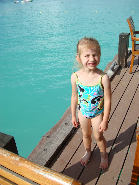 Young girl at end of pier next to water