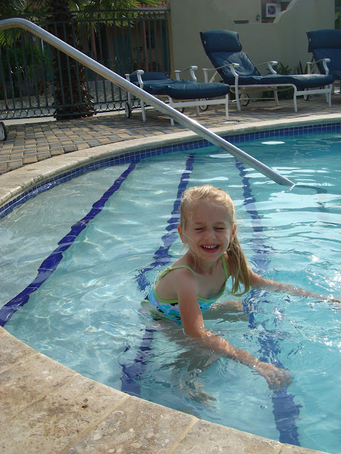 Young girl playing on steps in pool