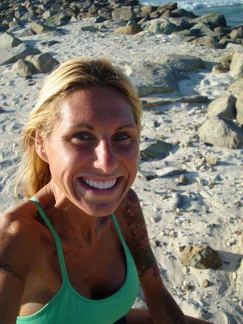 Woman on beach smiling in front of rocks