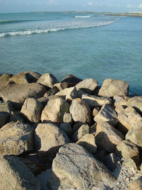Looking over pile of rocks into ocean